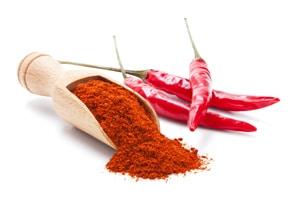 Warenkunde Chilipulver in Holzschaufel und Schoten